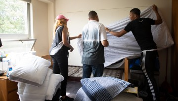 Student and family making the bed.
