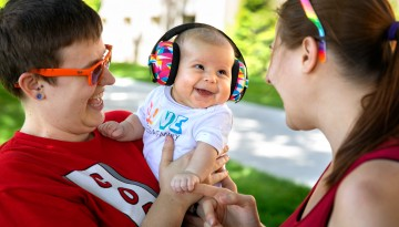 Two women with a smiling baby wearing noise-cancelling headphones.
