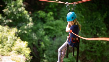 A reunion attendee on the zip line over Fall Creek Gorge.
