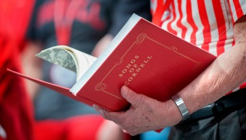 A man holds the hardcover 'Songs of Cornell' book.