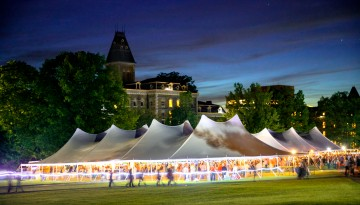 A tent on the Arts Quad lights up at dusk.