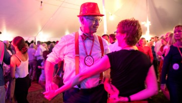 A couple dances under the tent.