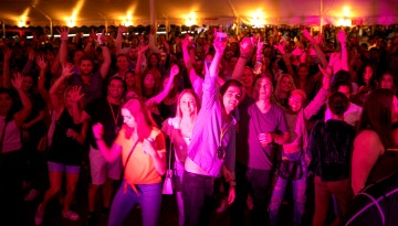 Reunion attendees cheering on the dance floor under the tent.