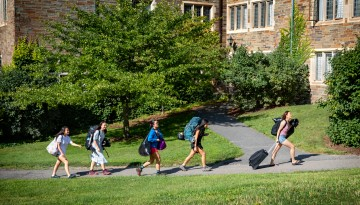 Students carrying luggage to the residence halls.