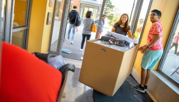 Students moving boxes into a residence hall.