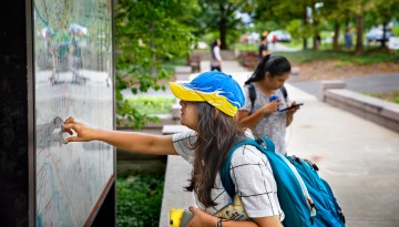 A new student checks out the campus map in front of Day Hall.