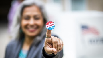 Woman holding voting sticker toward camera