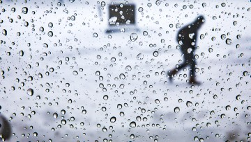 Drops of moisture cling to the window panes of Goldwin Smith Hall after a winter storm passes through.