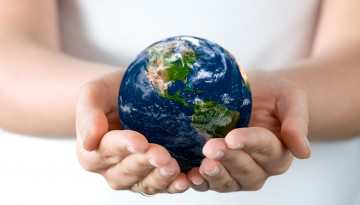 person holding mini globe in hand