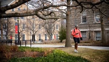 Student in shorts walking on campus