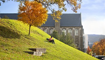 A student studies on Libe Slope in fall