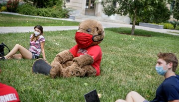 Big Red bear sitting with students in mask