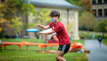 Students play frisbee and football on the Arts Quad