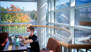 A student studies on the third floor of Statler Hall as fall colors peek in the windows
