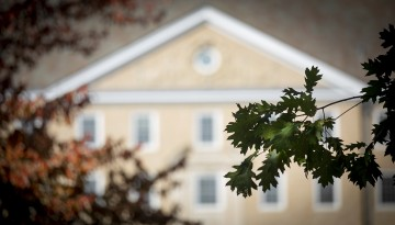 A newly-renovated Martha Van Rensellaer Hall peeks through the trees on a bright fall day.