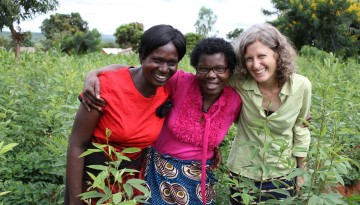 three women stand in a field and smile